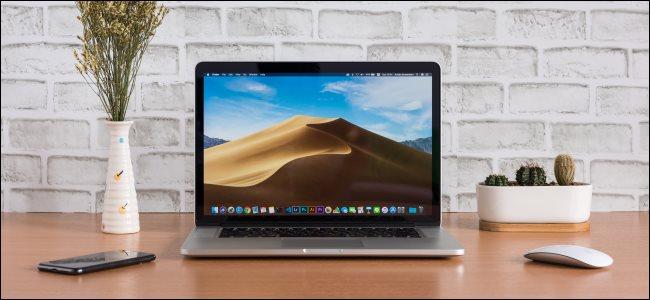 Um MacBook aberto em uma mesa ao lado de um mouse e smartphone.