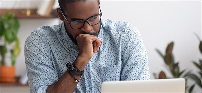 Um homem olhando fixamente para seu laptop.