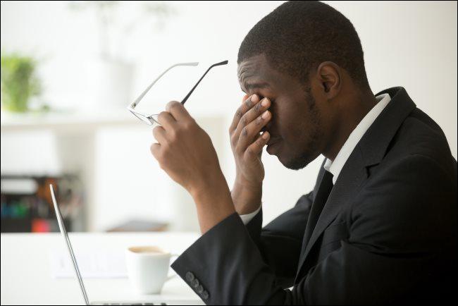 Um homem sentado na frente de seu laptop, segurando os óculos e esfregando os olhos.