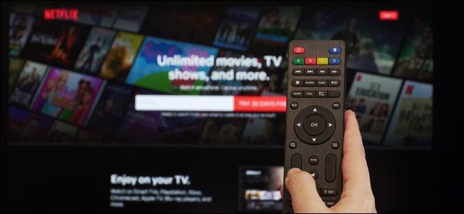 Uma mão segurando um controle remoto em frente à tela de inscrição da Netflix em uma TV.