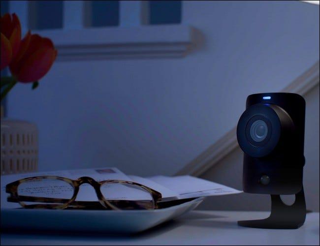 Câmera ao lado de copos na mesa à noite