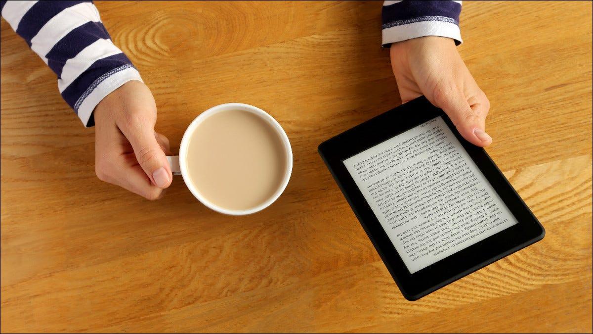 Pessoa lendo o Kindle enquanto bebe café.