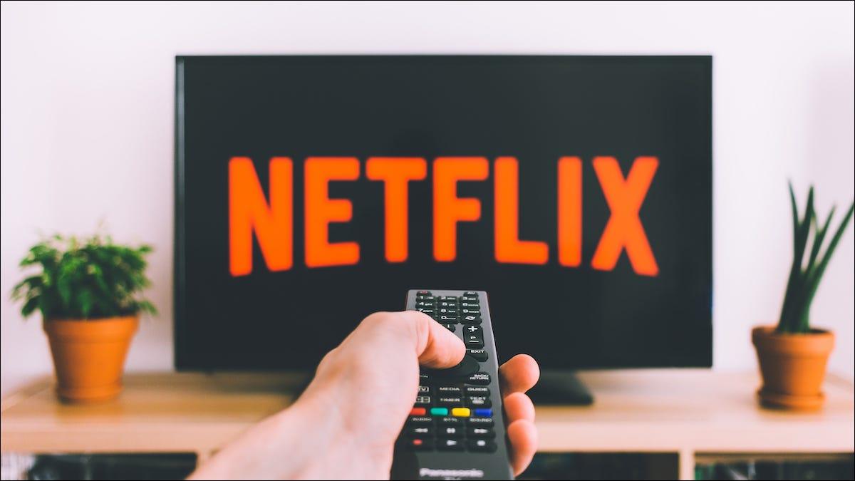 Pessoa apontando um controle remoto em direção a uma TV com o logotipo da Netflix
